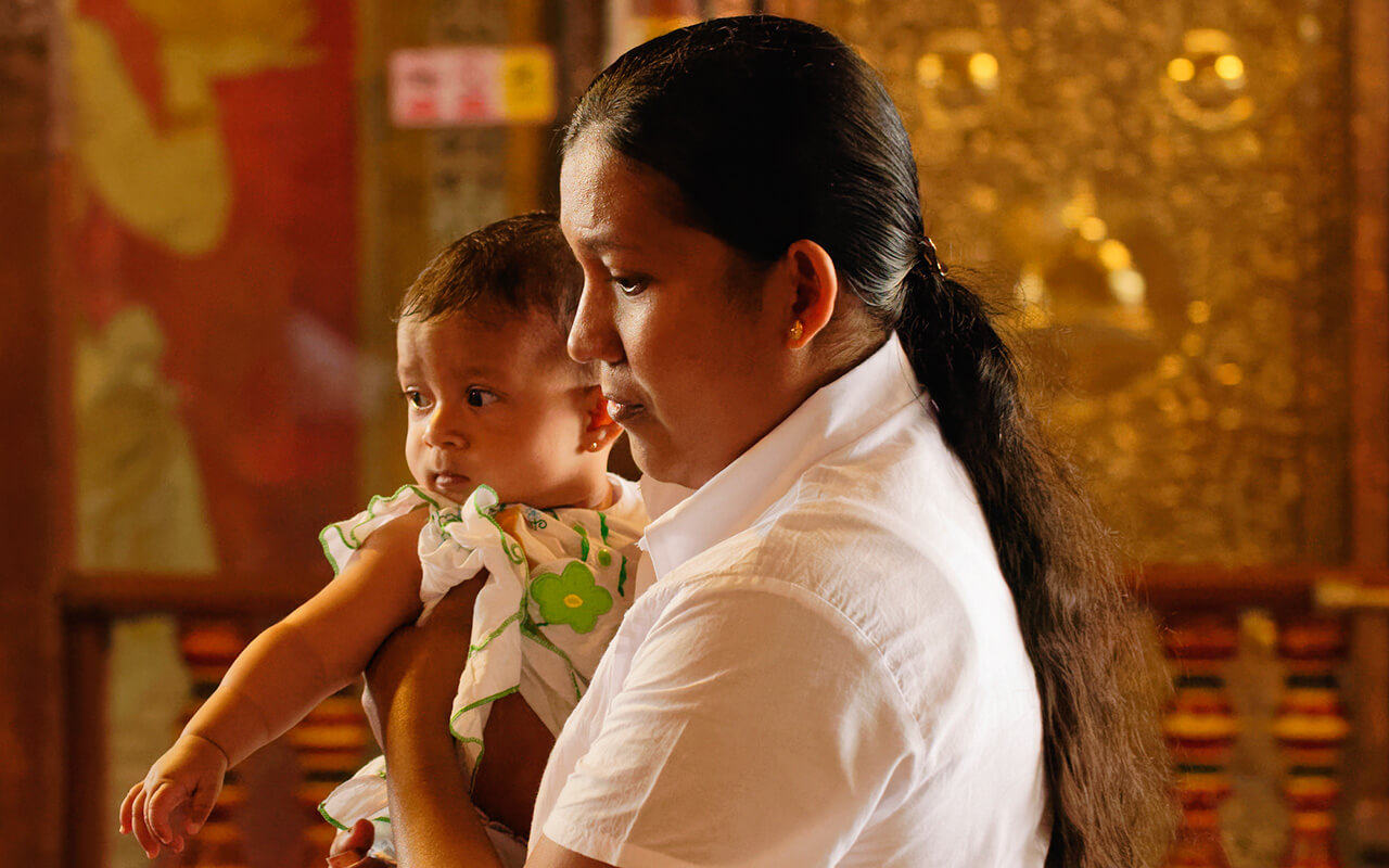 Woman and her baby to be blessed at the Temple of Tooth in Kandy Sri Lanka